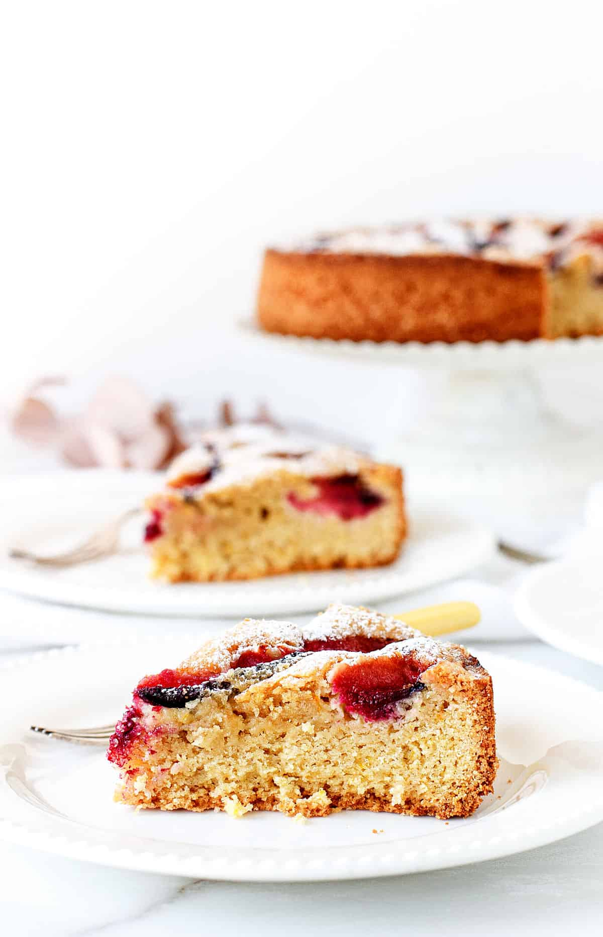 Slices of plum cake on white plates, cake on white cake stand, white background