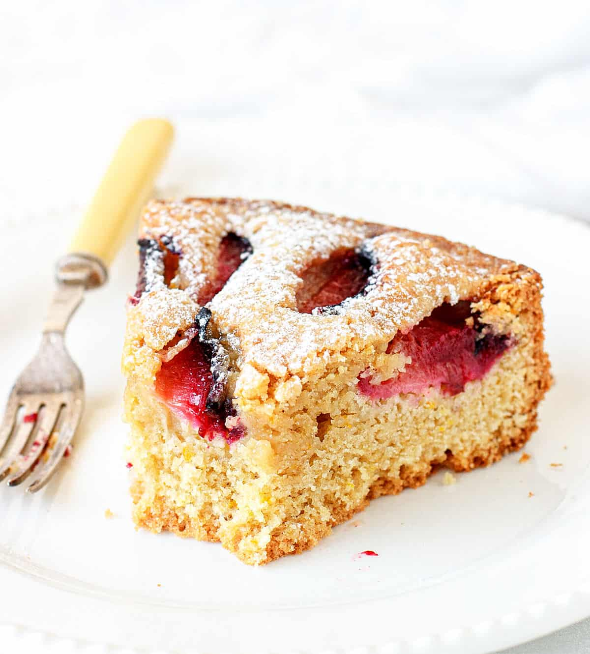 Eaten slice of plum cake on a white plate, silver yellow fork, white background