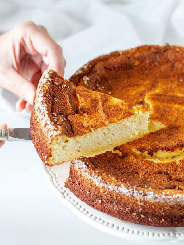 Lifting slice of golden ricotta cheesecake with cake server