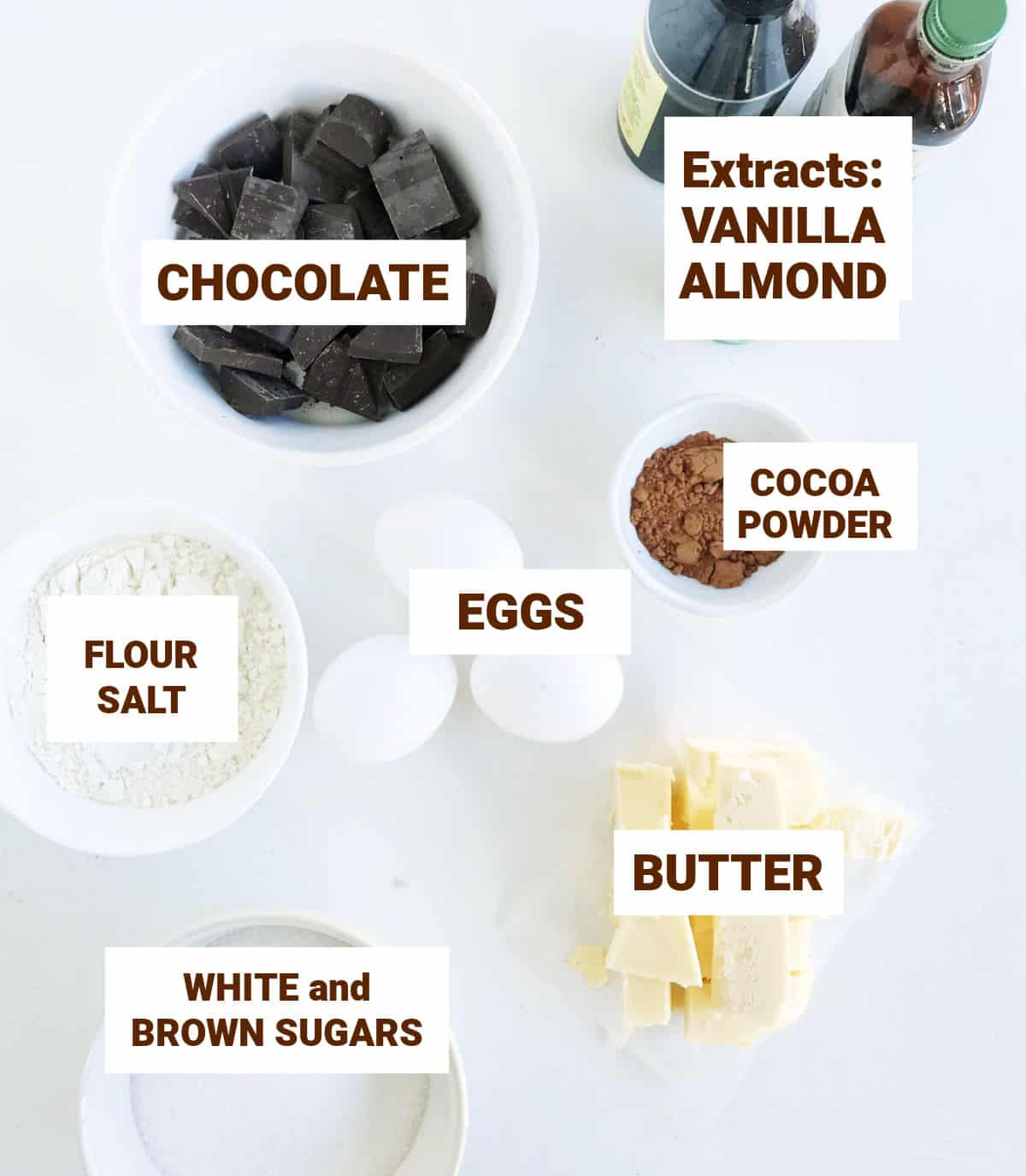 White surface with bowls containing ingredients for brownies, including extracts, cocoa powder, chocolate and whole eggs