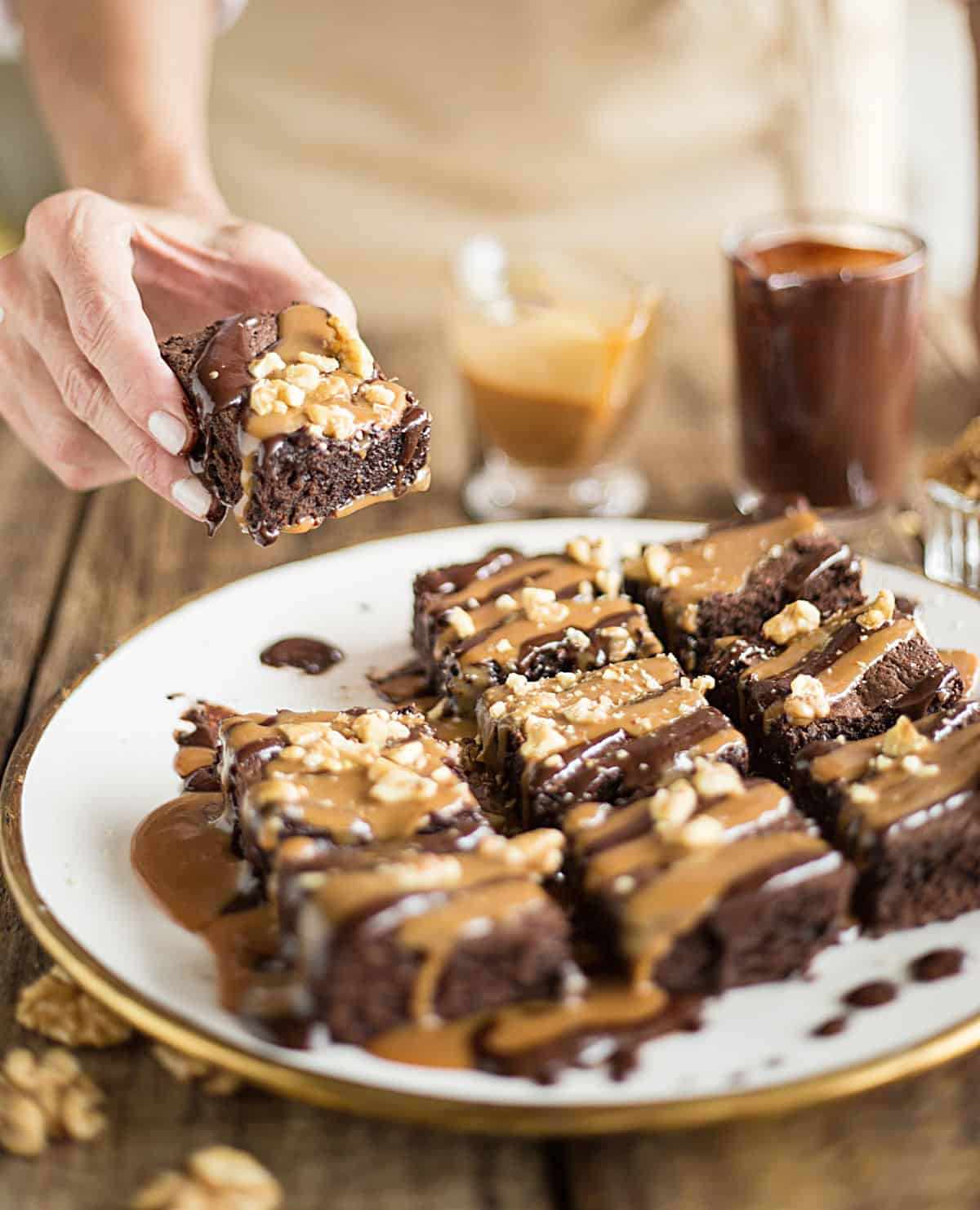 Plate of chocolate and dulce de leche sauced brownies on white gold plate; hand holding one