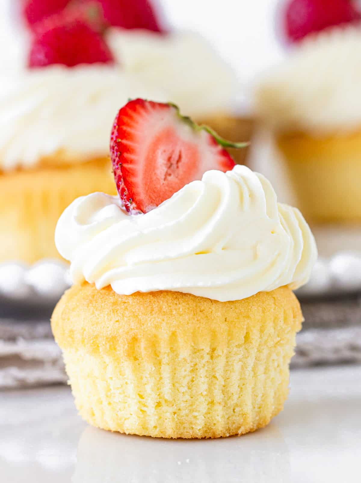 Single strawberry cream vanilla cupcake on white surface, more cupcakes blurred in background
