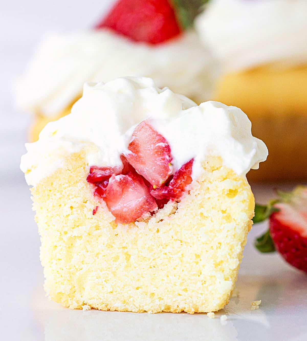 Close up of cut vanilla cupcake filled with strawberries and whipped cream