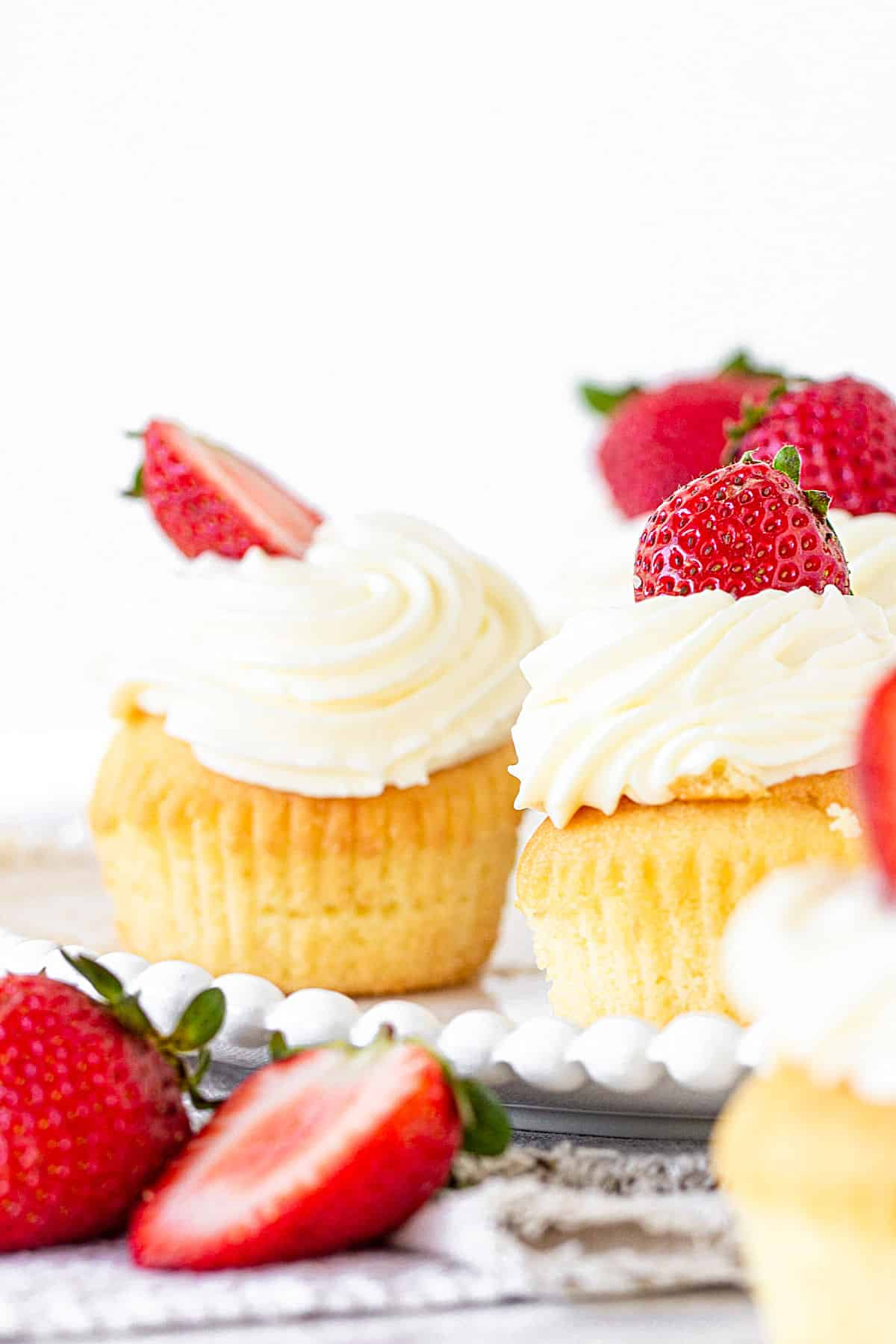 Two cupcakes topped with whipped cream and strawberries, white background, fresh strawberries