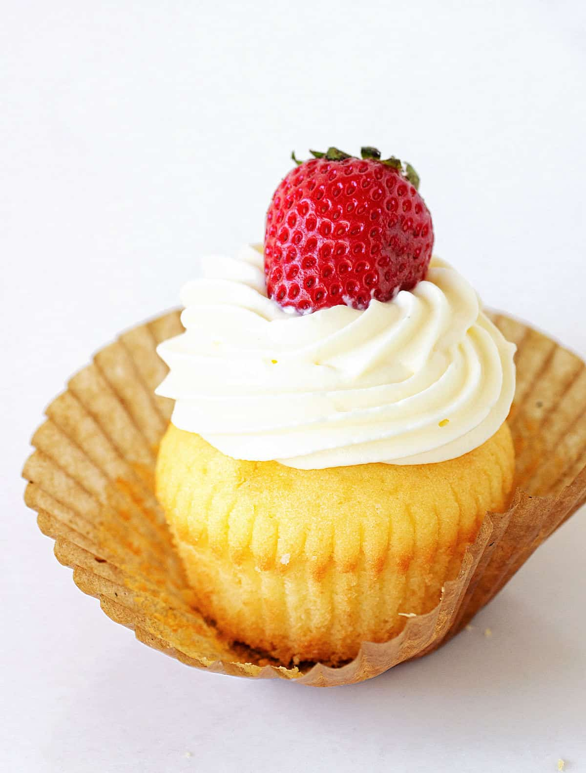 On white surface a vanilla cupcake topped with cream and strawberry in a brown paper liner