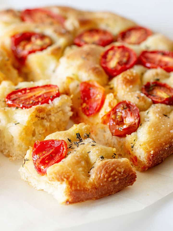 Close up of round tomato focaccia bread cut in squares on white surface