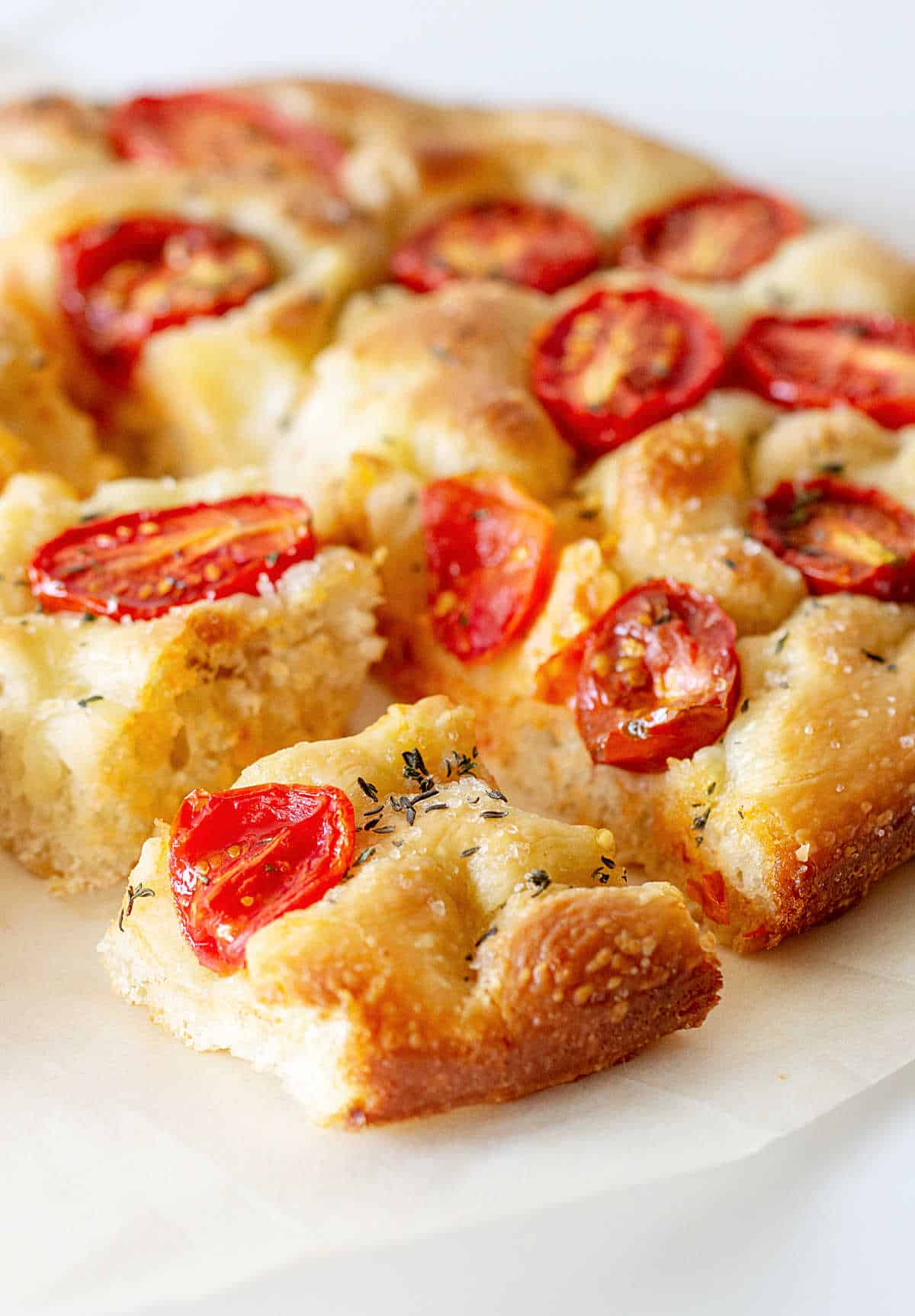 Tomato focaccia cut in squares on white surface