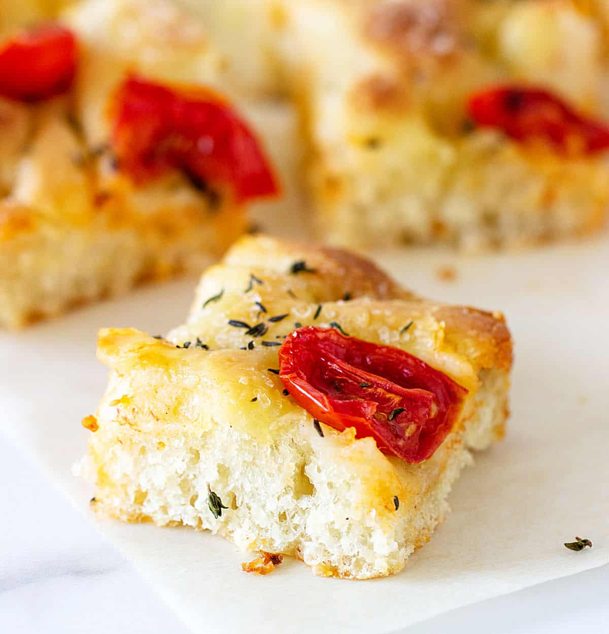 Single square of focaccia with tomato on white surface