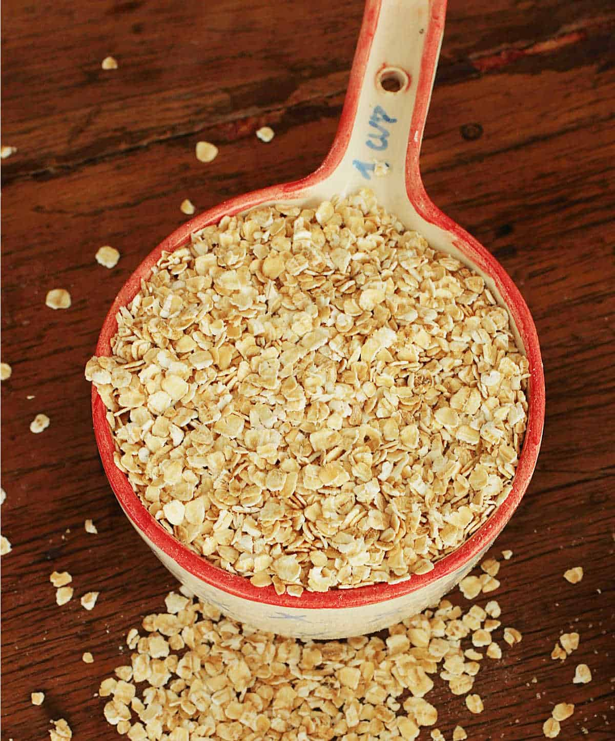 Ceramic measuring cup overflowing with oats on wooden table