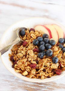White bowl filled with granola, apples and blueberries, with wooden spoon, on white table