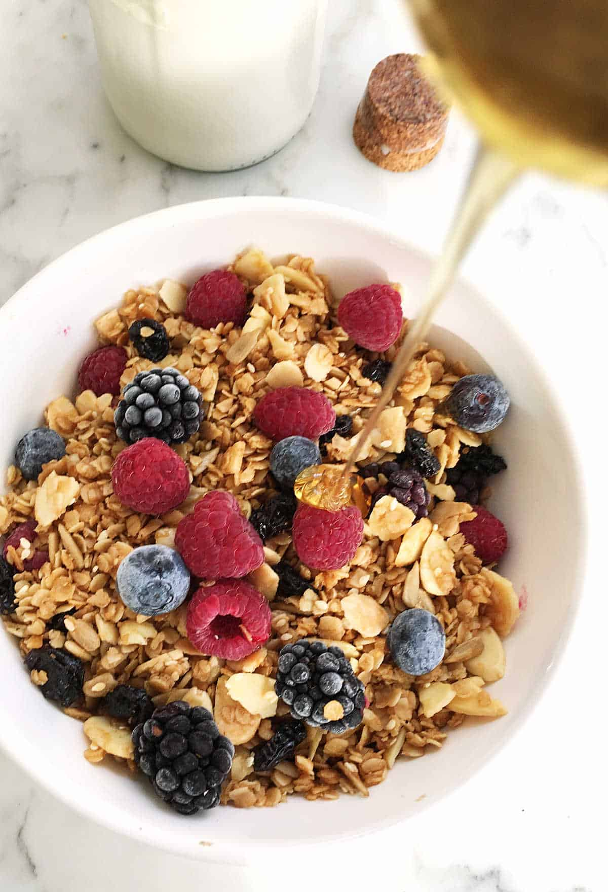 Drizzle of honey pouring onto a white bowl with granola and berries, white surface, milk bottle