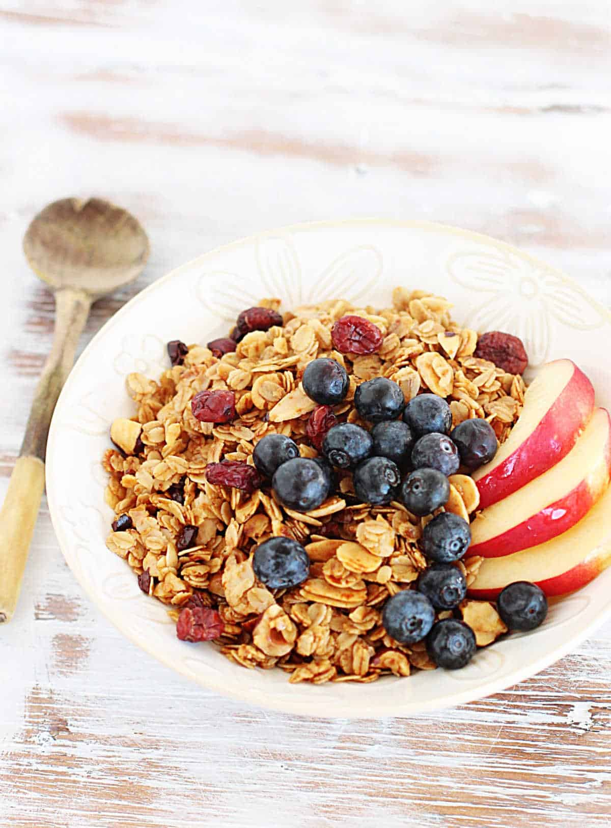 Whitish table with white bowl with granola and fruit, a wooden spoon beside it
