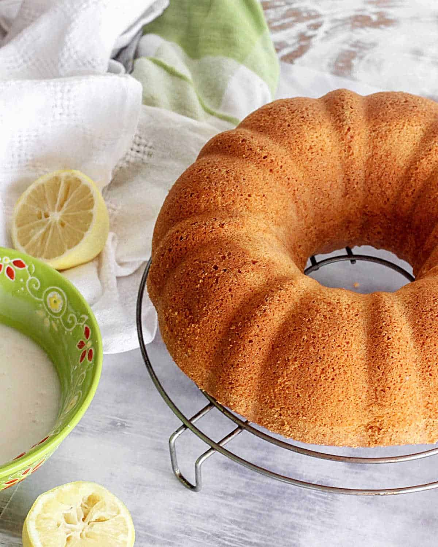 Unglazed bundt cake on wire rack on a white table, green white towel, bowl, and lemon halves