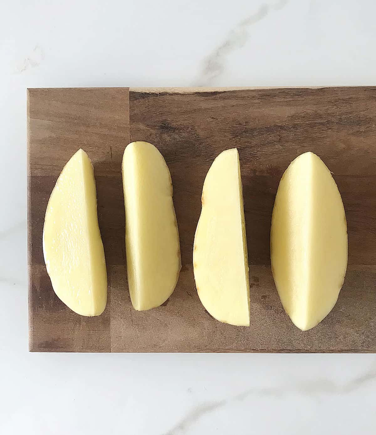 Wooden board with four raw potato wedges