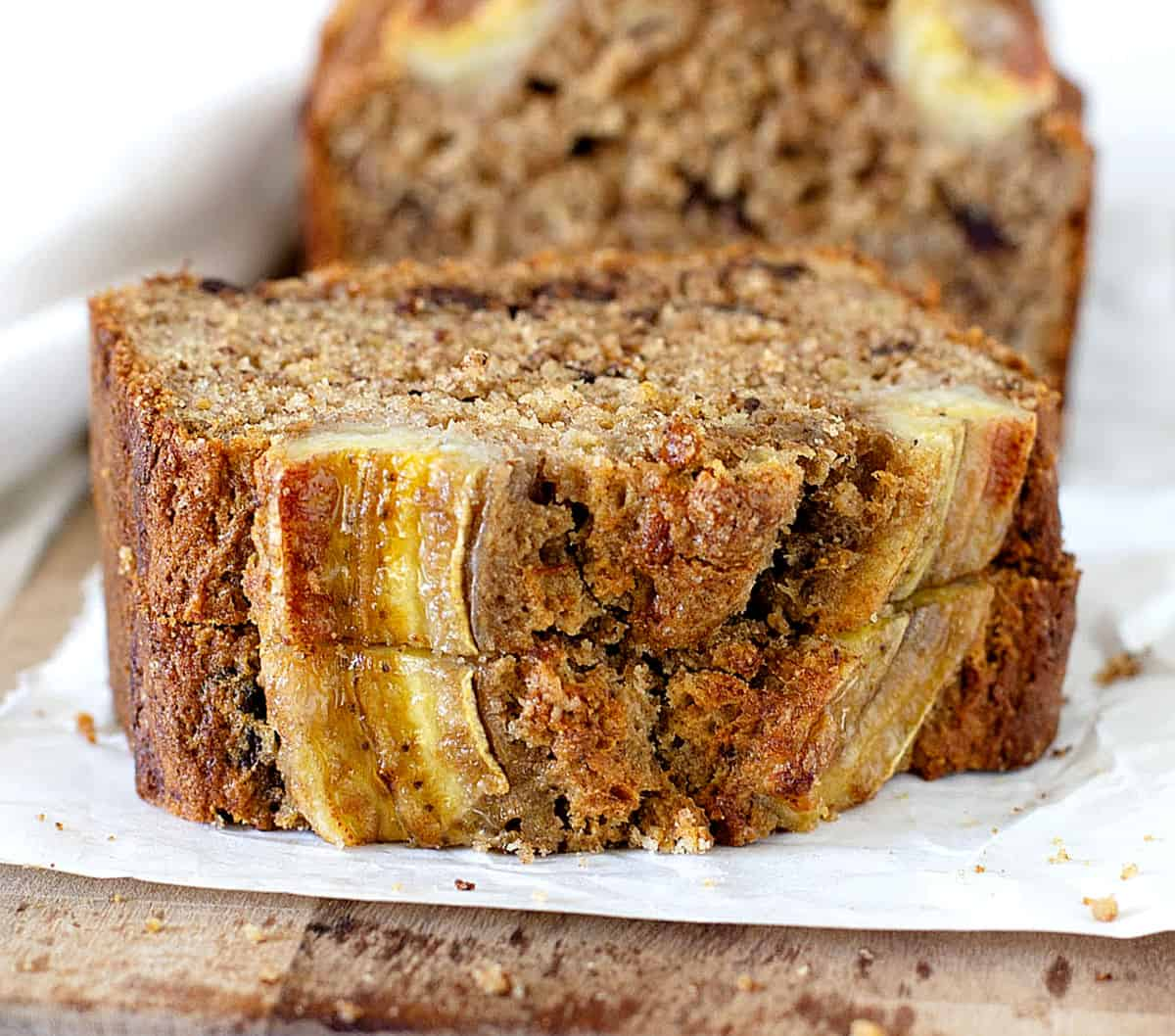 Two stacked slices of banana bread on white paper