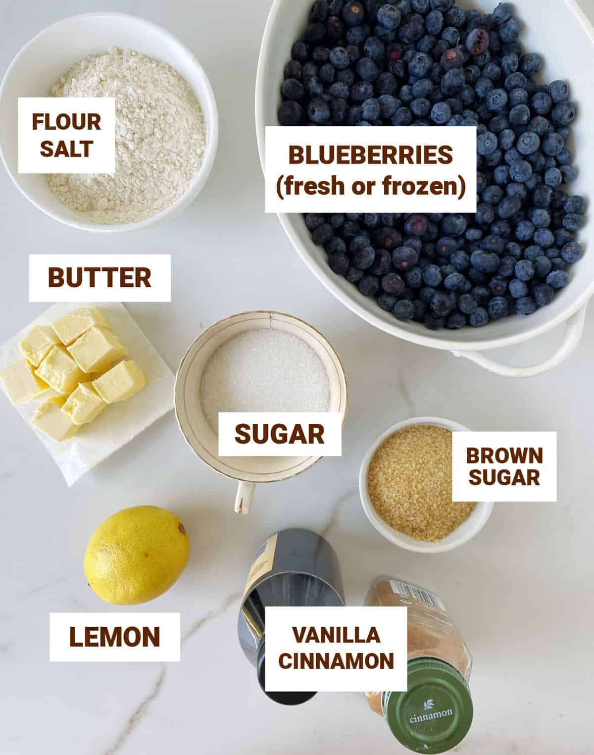 Ingredients for blueberry crumble in bowls on white surface including lemon, butter, vanilla and cinnamon
