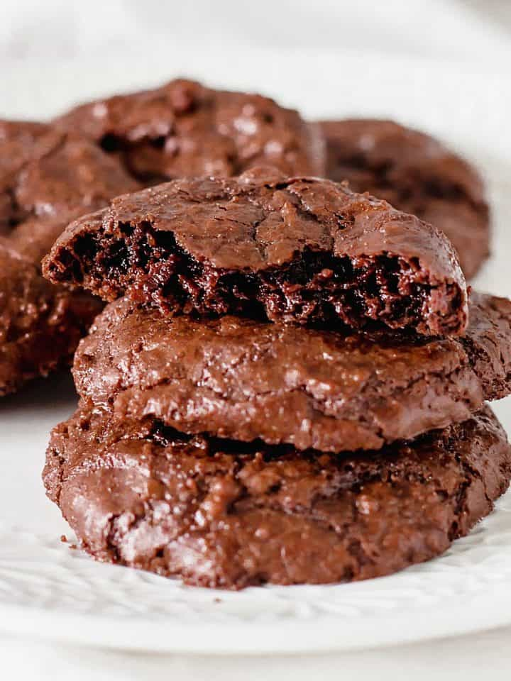 Close up or chocolate cookie stack with top one bitten, white background