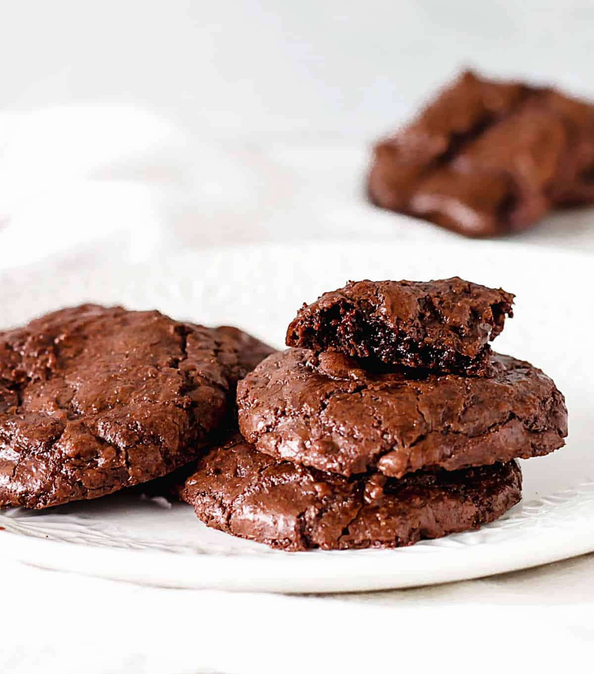 White plate with brownie cookies, whole and eaten; greyish background