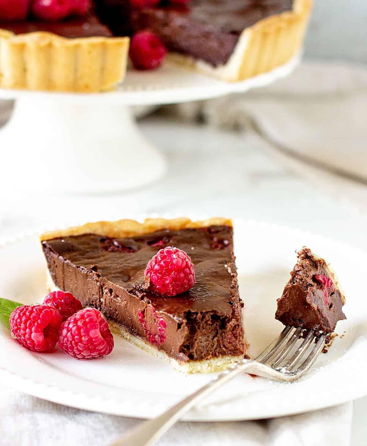 Slice of chocolate raspberry tart, on white plate, silver fork, tart on background