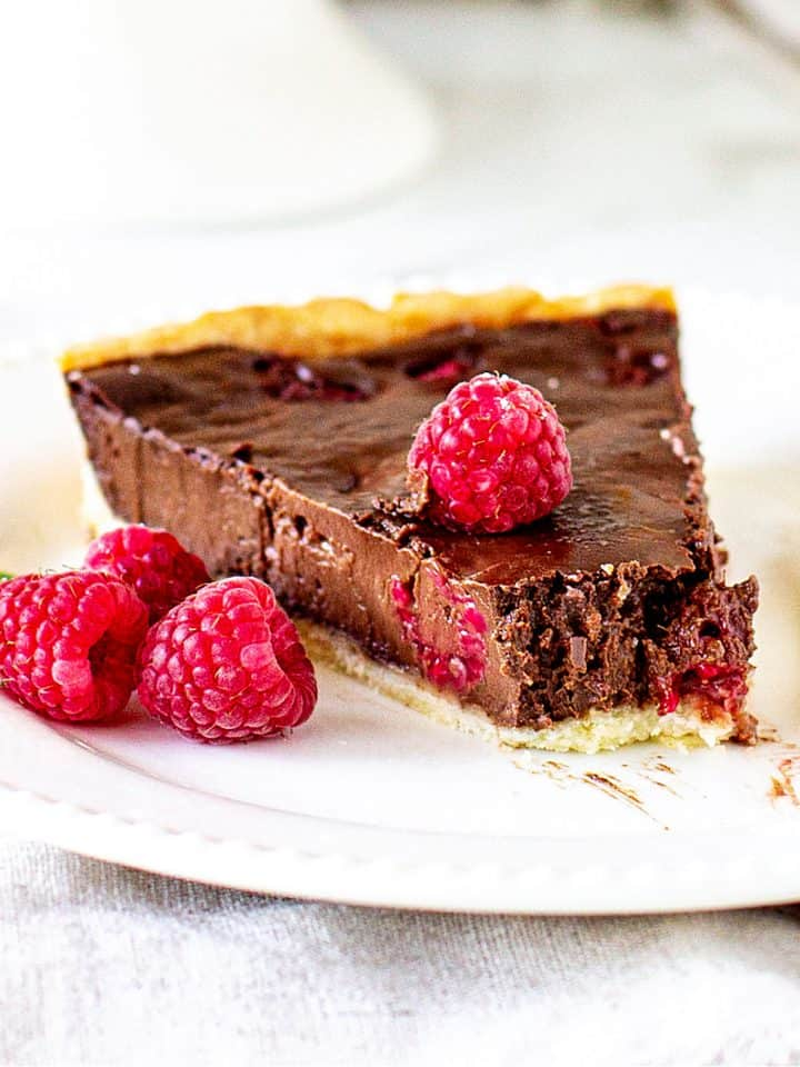 Singles slice of raspberry chocolate tart on white plate, whole raspberries, white background