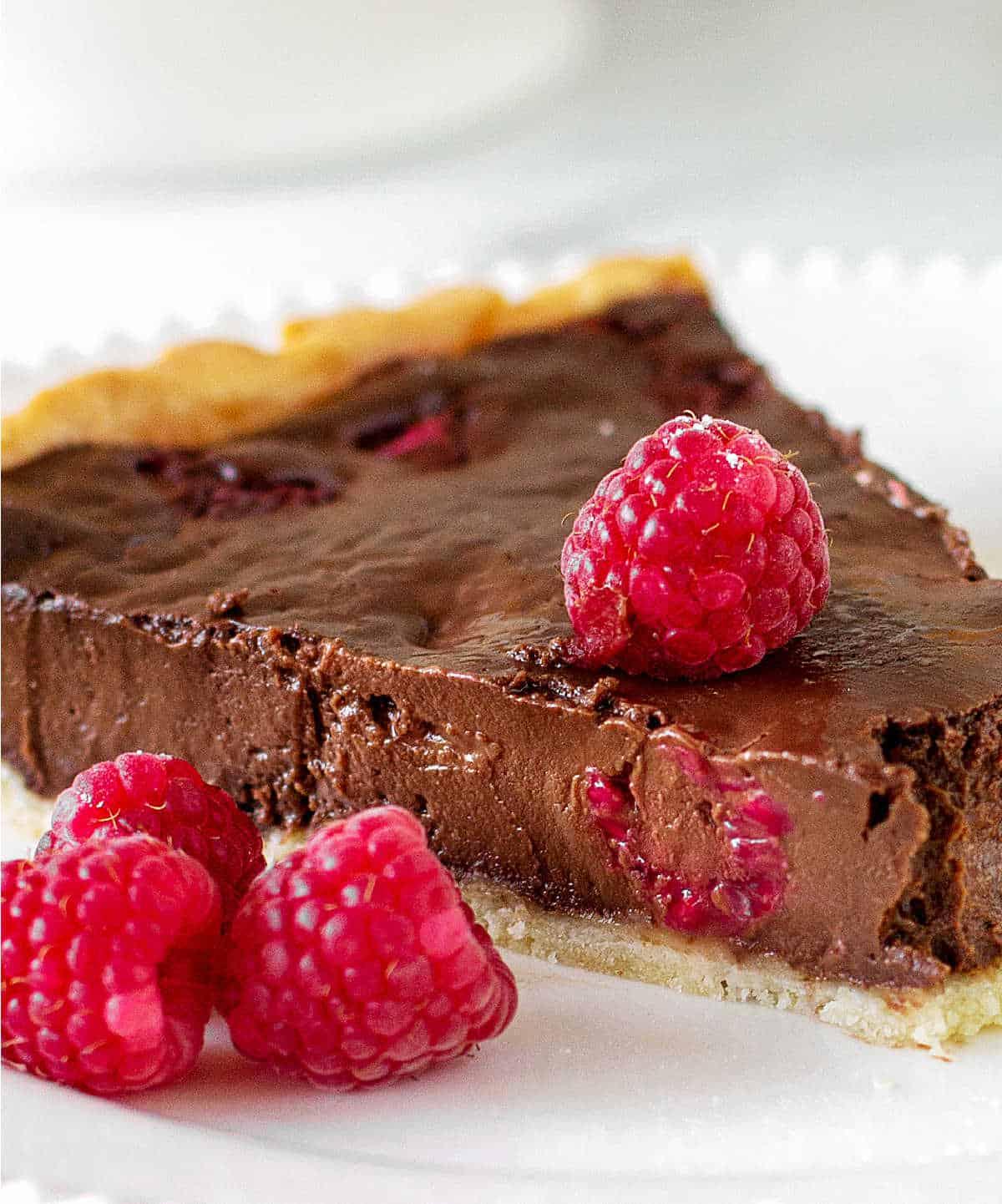 Close up slice of chocolate raspberry tart on white plate