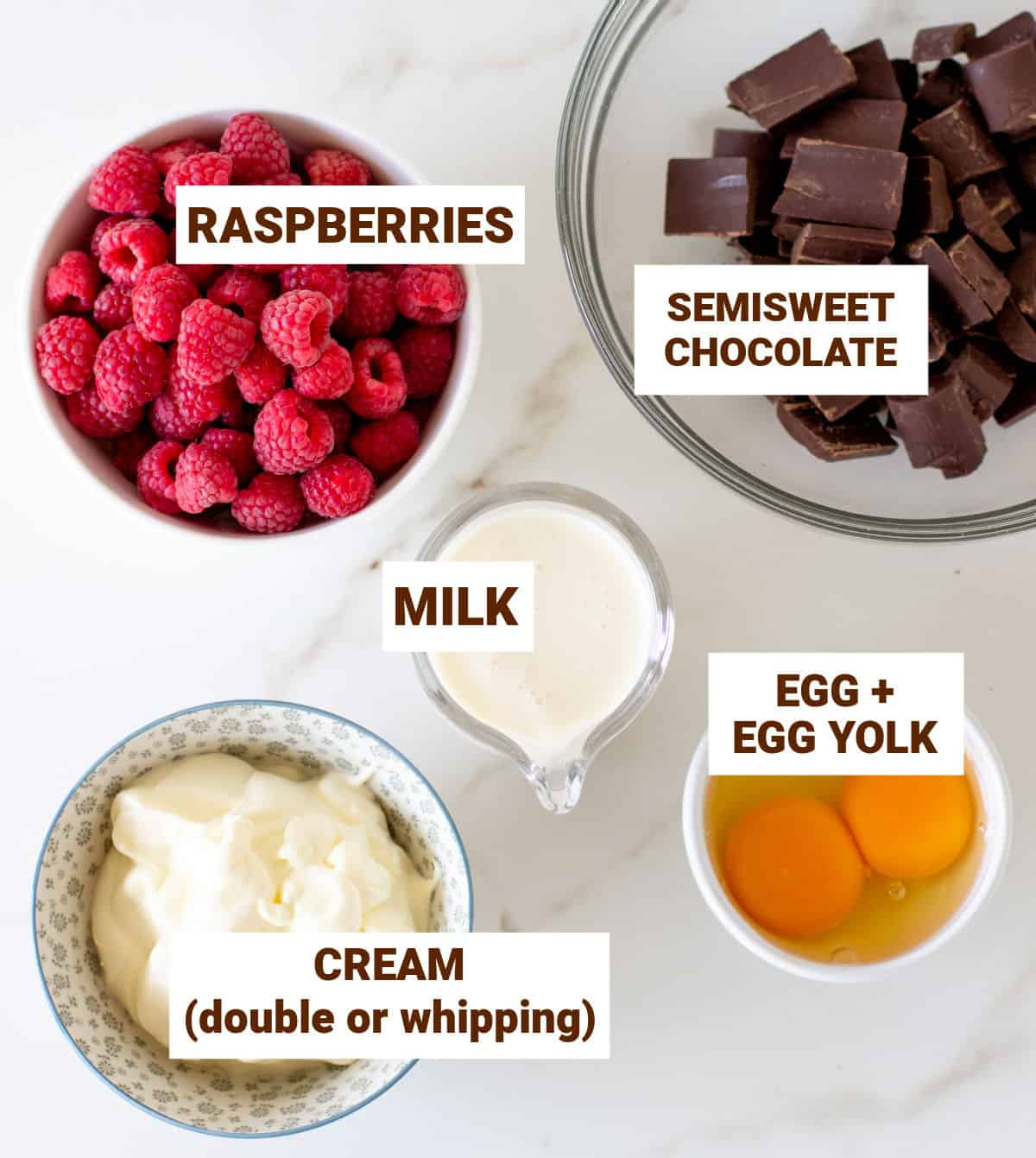 Raspberries, chocolate eggs and cream in bowls on white surface