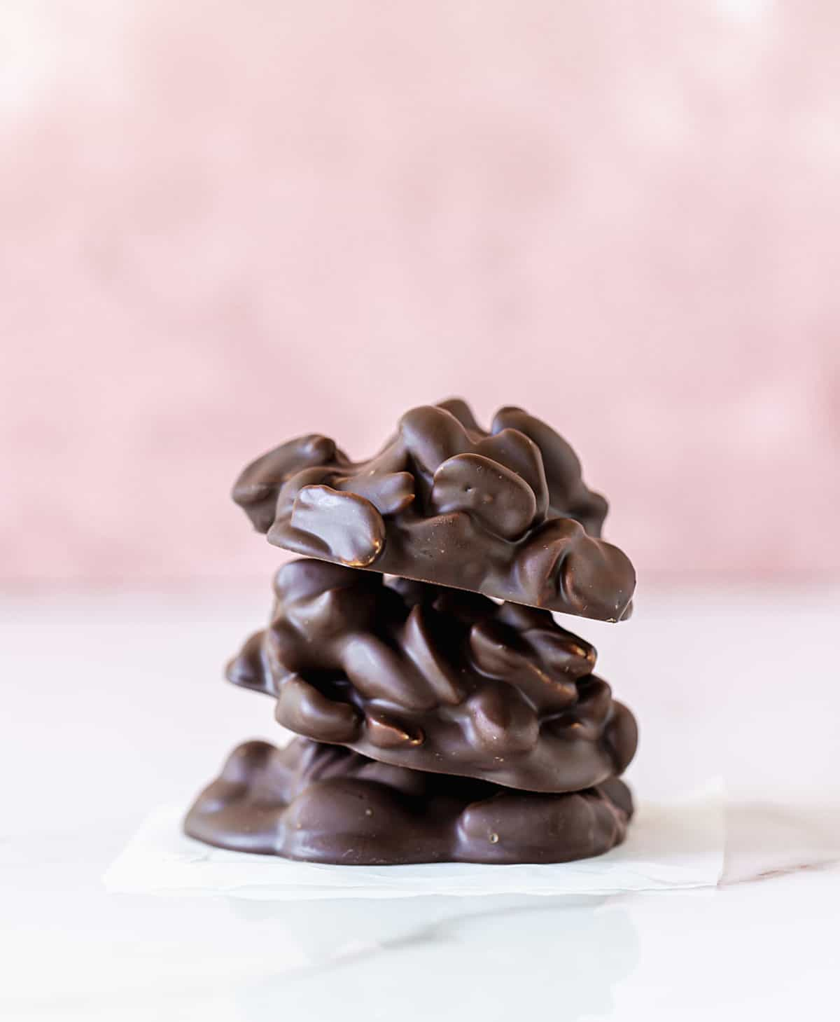 Stack of three chocolate peanut clusters on white and pink background
