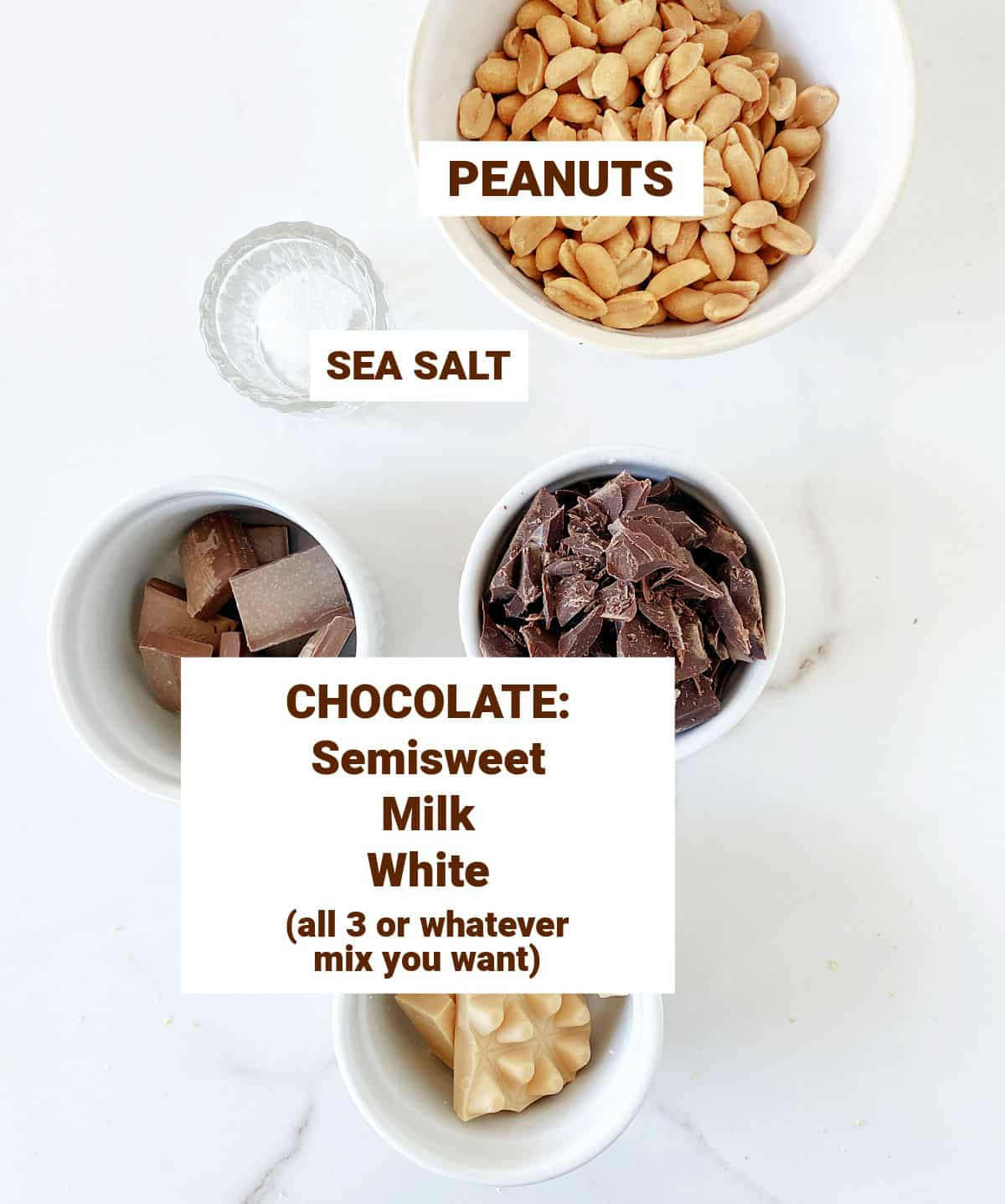 White surface with bowls containing different chocolates, peanuts and salt