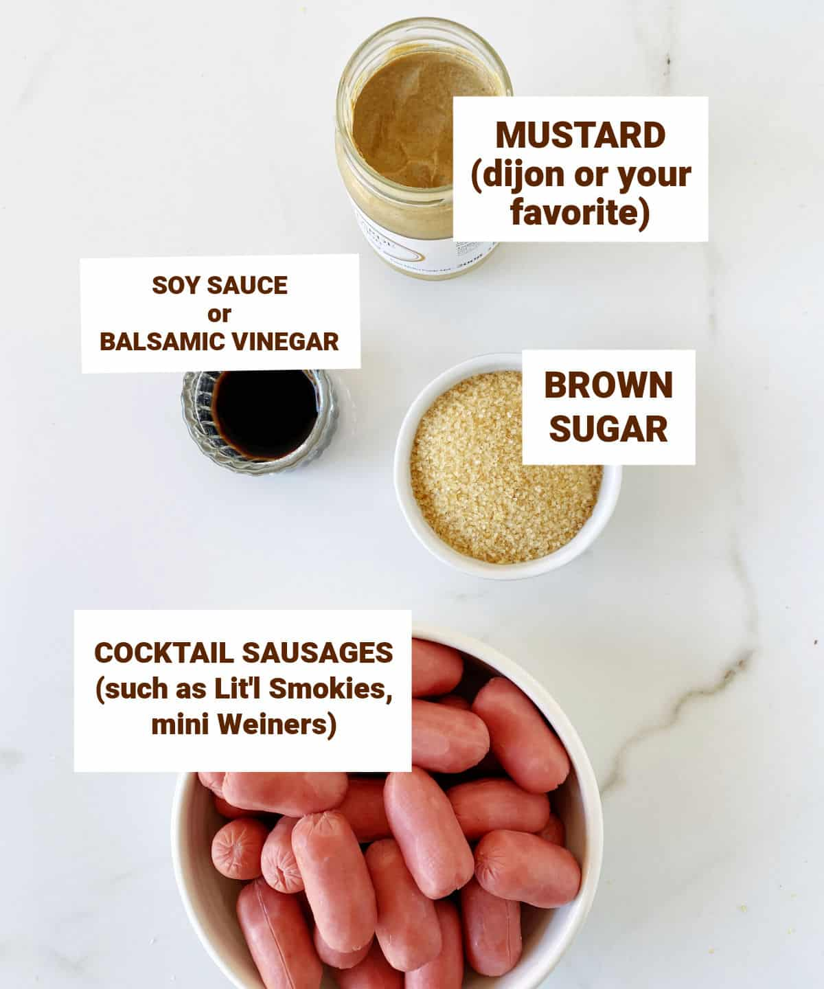 White marble surface with 4 bowls with ingredeints for cocktail sausages including mustard, brown sugar and soy sauce