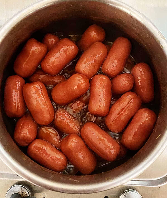 Small sausages boiling in metal saucepan