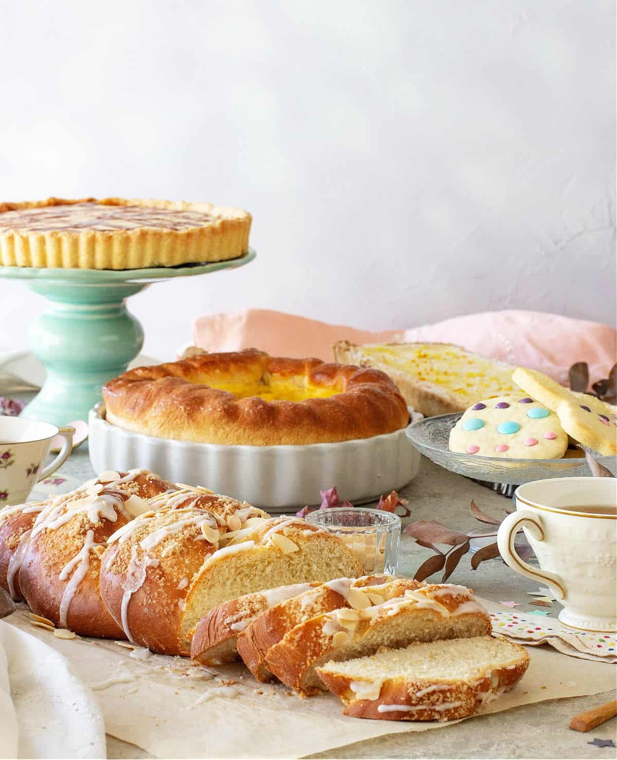 An Easter brunch table with a pie on a green stand, cookies, braided breads, a pie, a cup of tea