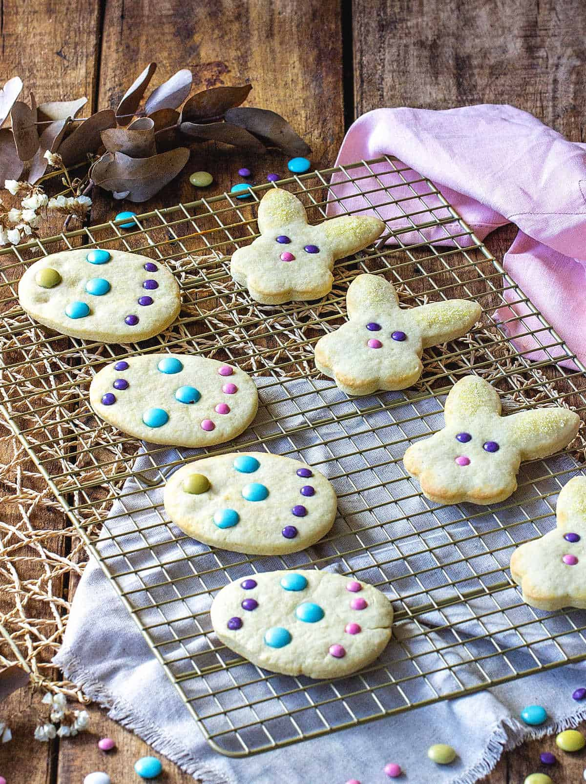 Several Easter sugar cookies on wire rack over wooden table with linens