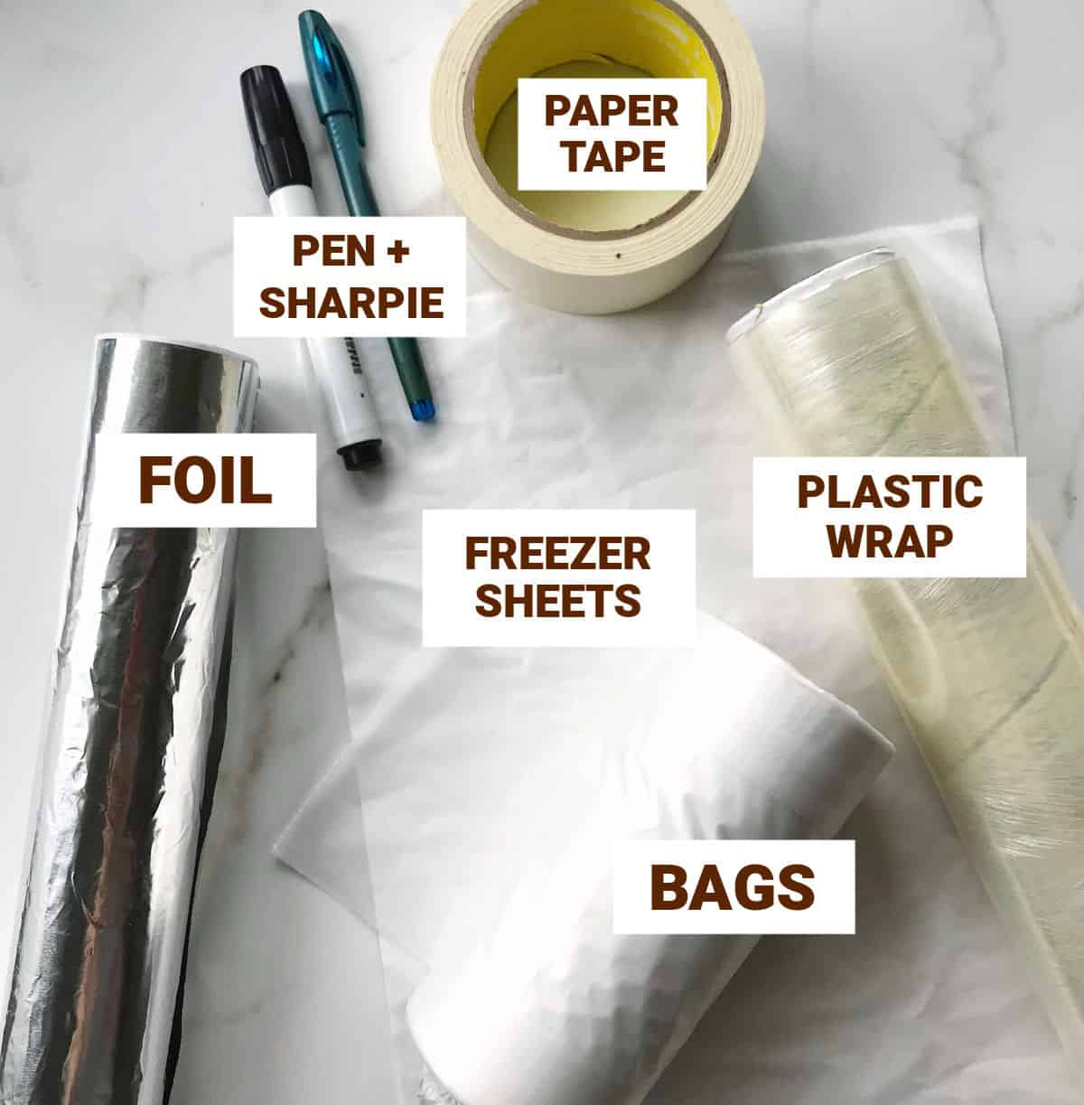 Pens, foil and plastic wrap, tape, bags on white marble surface
