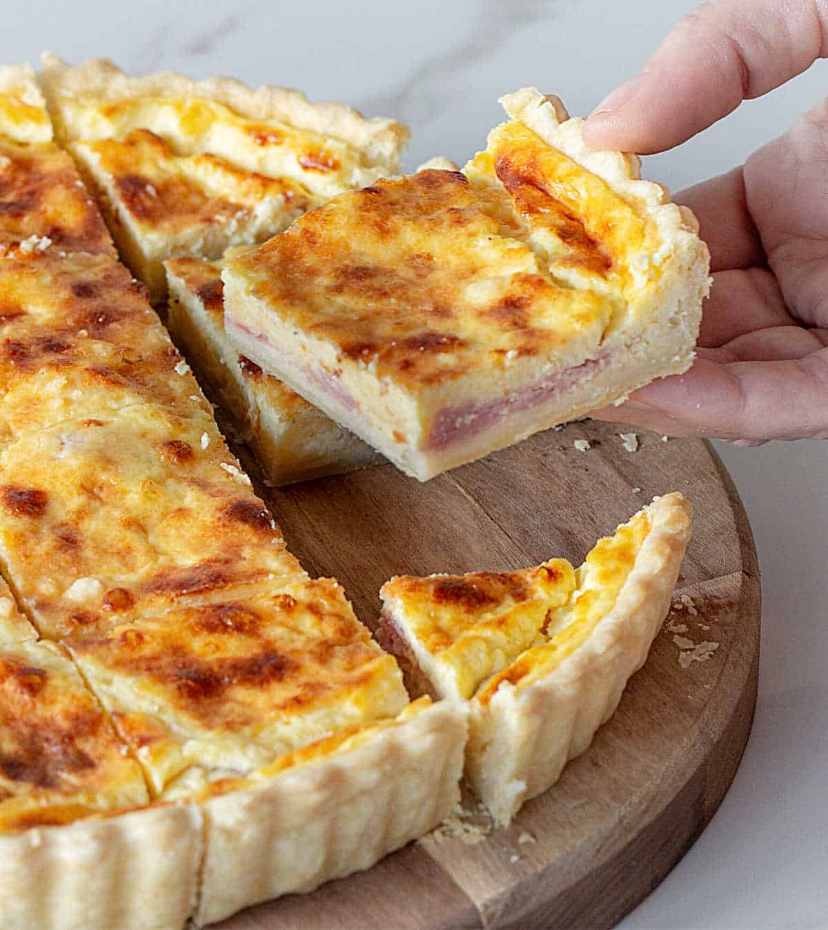 A hand lifting square of ham and cheese quiche on wooden board