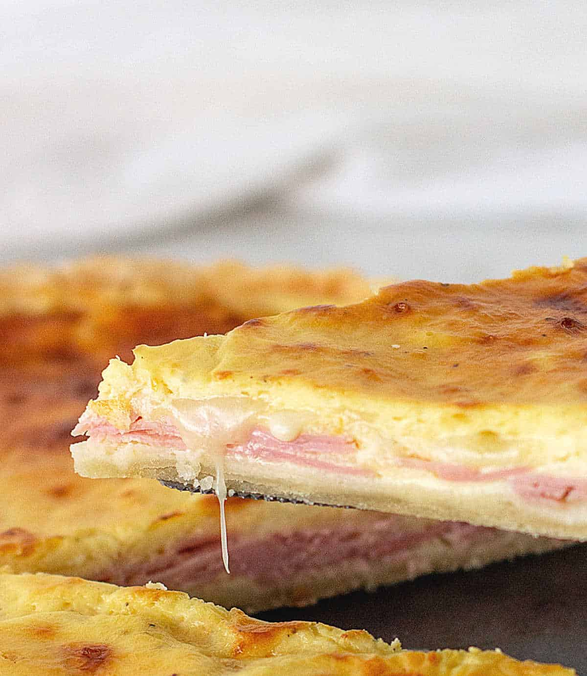 Lifting slice of ham and cheese quiche, melting cheese