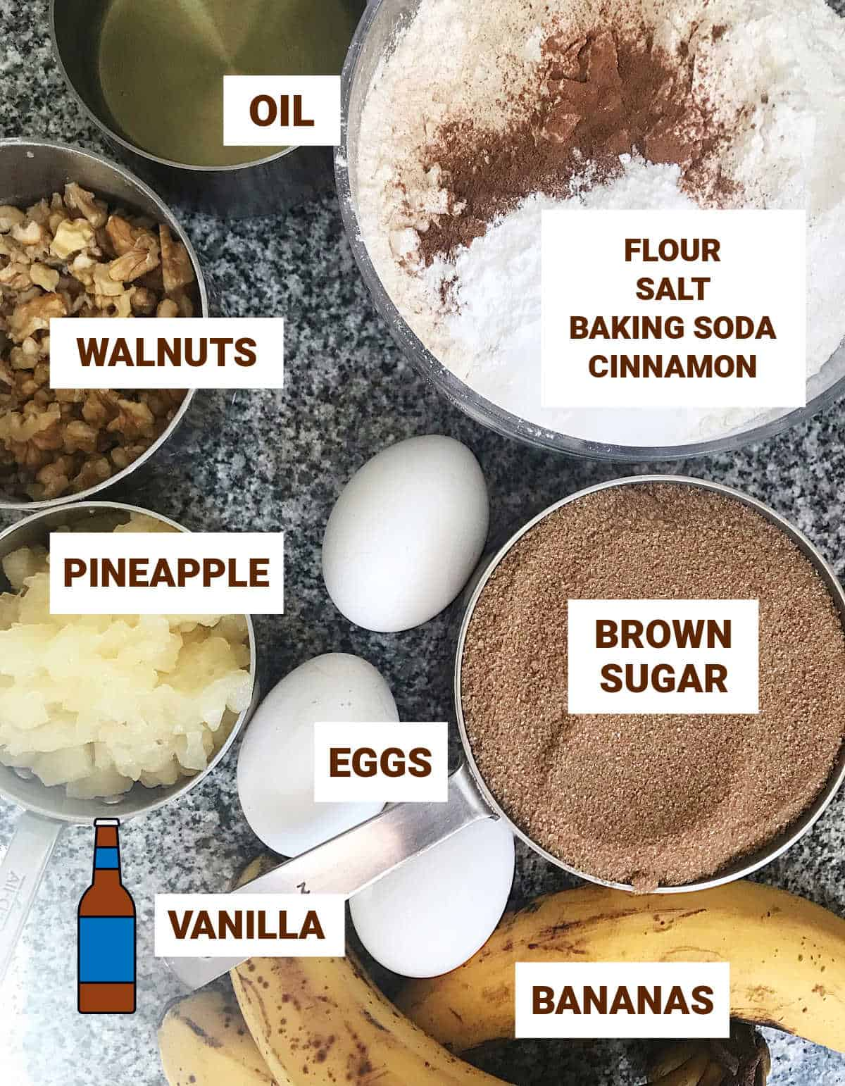 Hummingbird layer cake ingredients in bowls on grey surface including pineapple, bananas, eggs and walnuts
