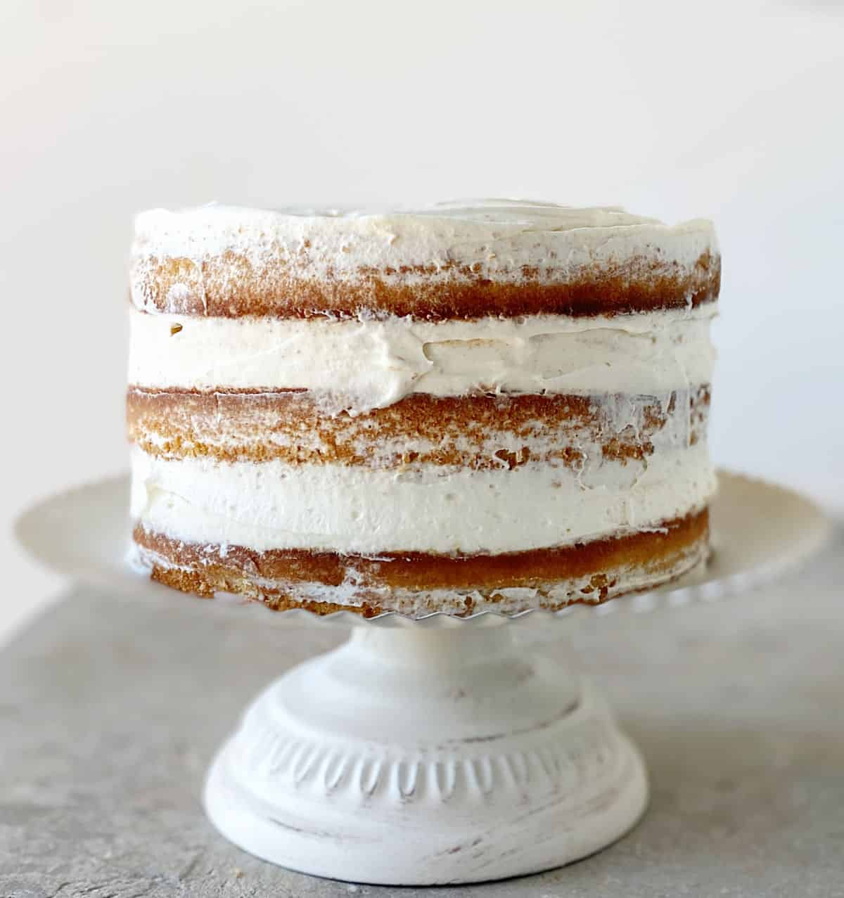 Frosted naked layer cake on white cake stand on grey surface