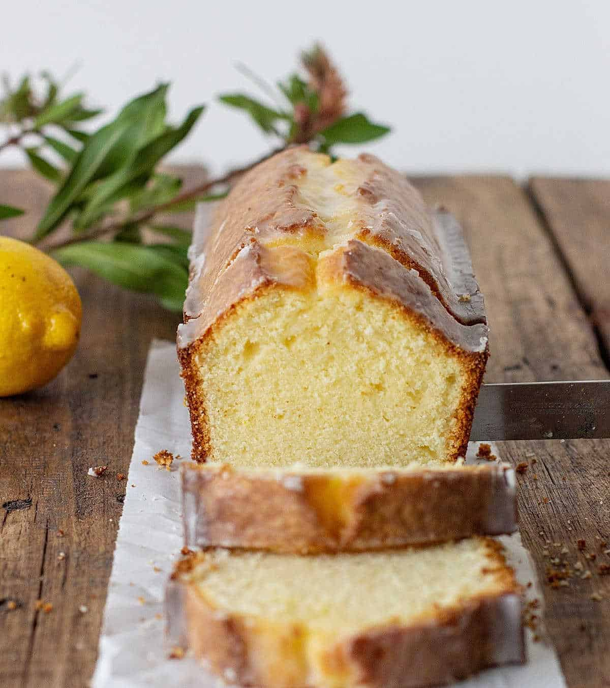 Half pound cake with slices on wooden board, a lemon, green branch and knife
