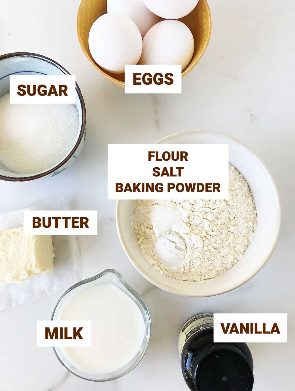Different bowl with shortcake cupcake ingredients including eggs, butter, milk, vanilla bottle