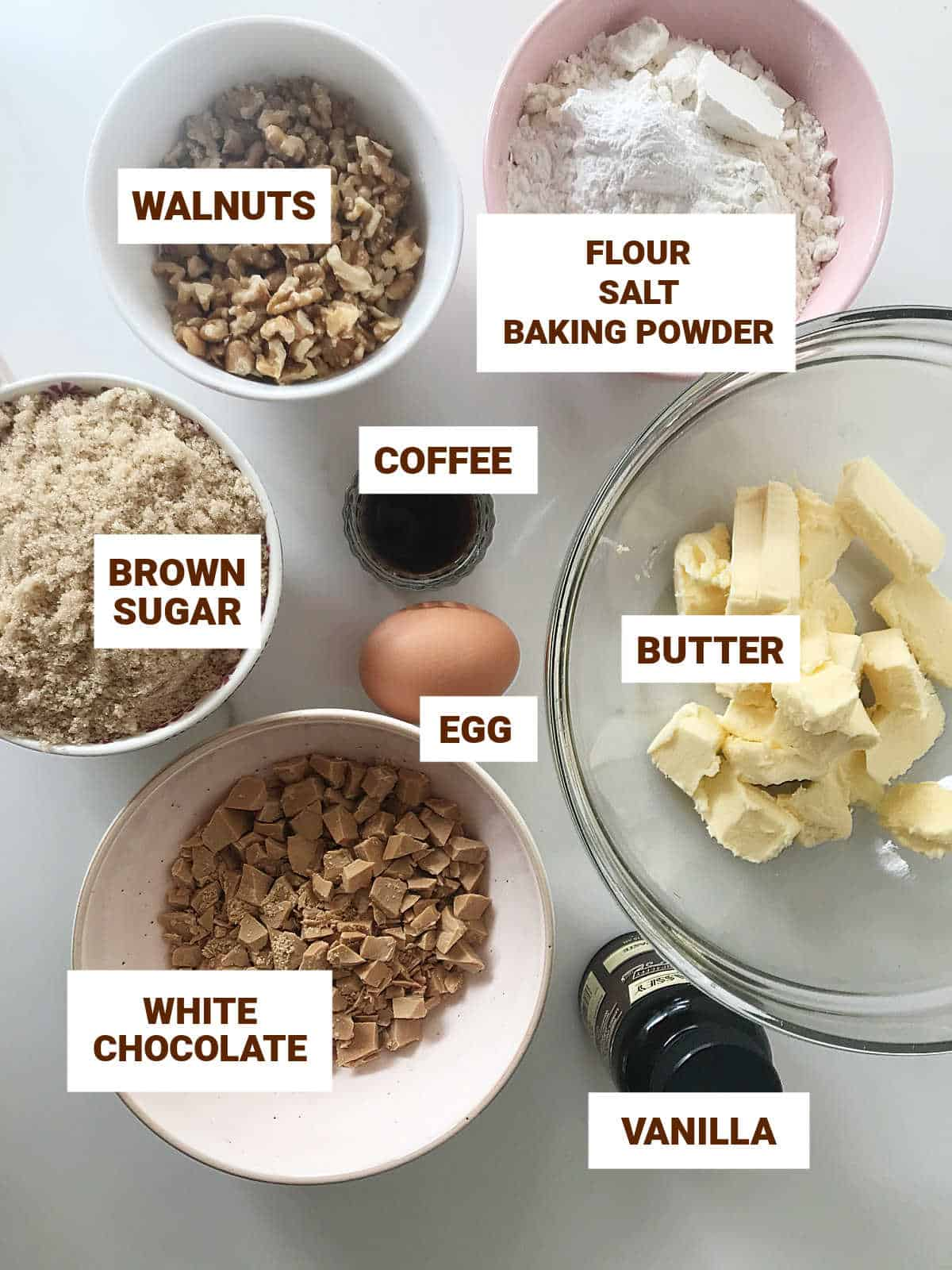 White chocolate blondies ingredients in bowls on white surface including walnuts, coffee, egg, and vanilla