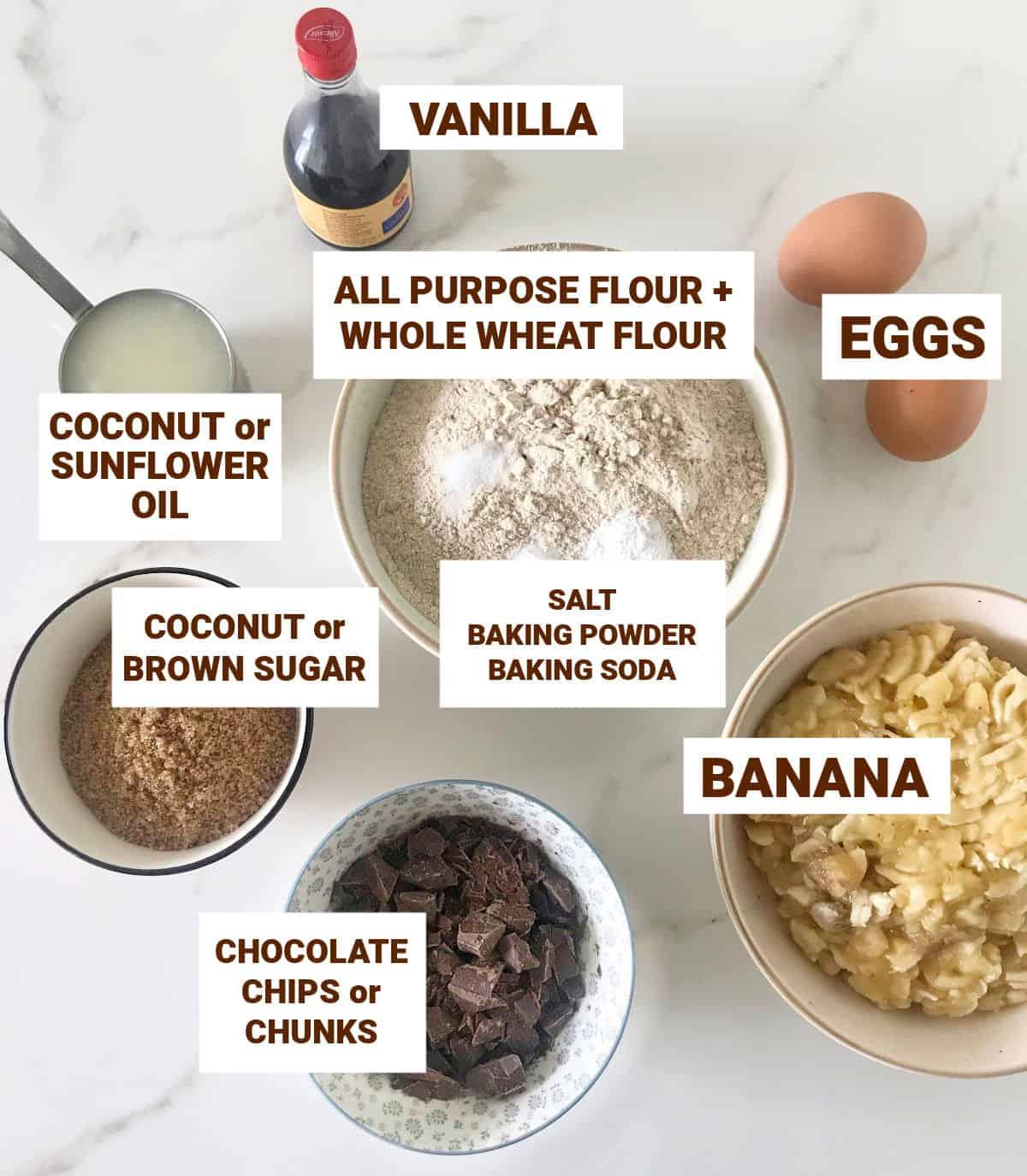 Banana chocolate bread ingredients in bowls on white surface, including eggs, vanilla and chocolate chunks