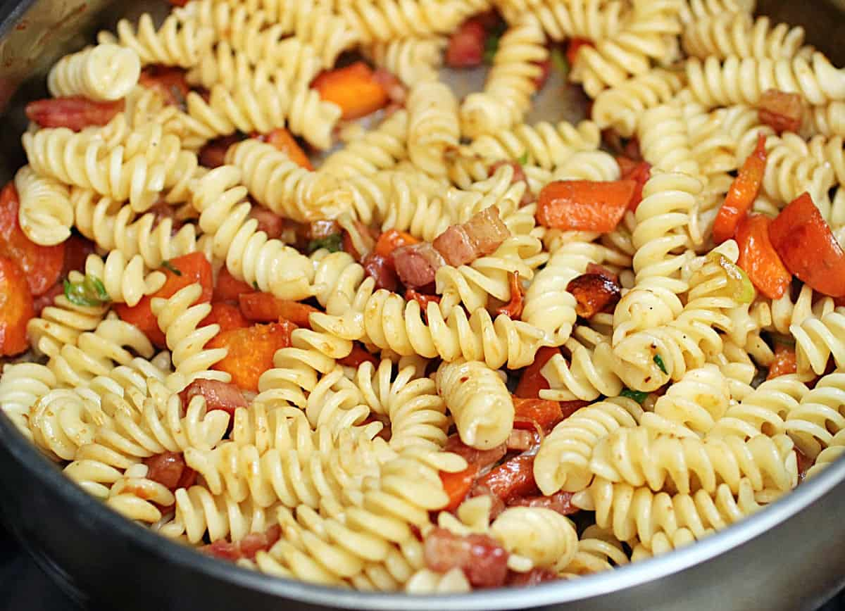 Close up of fusilli pasta with carrots in metal skillet