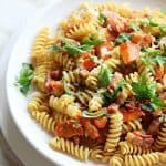 White plate with fusilli pasta, carrots, bacon and chopped parsley