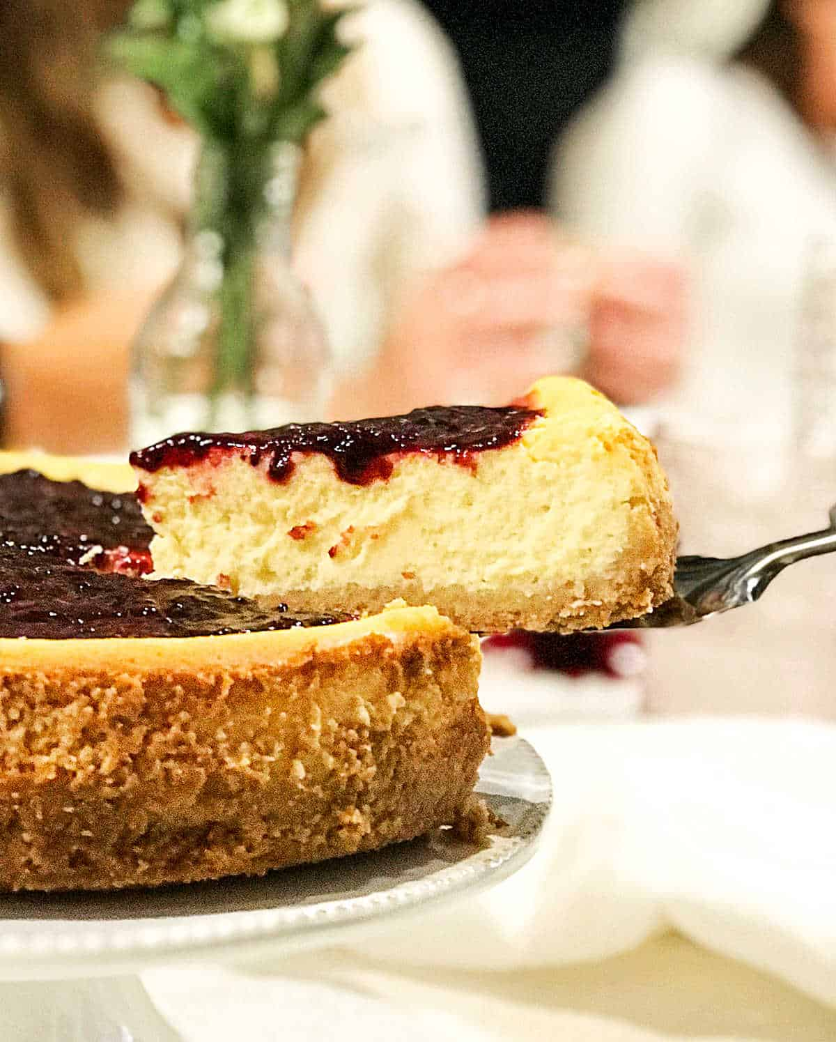 Round cheesecake in table with people in background, a slice being lifted with a cake server
