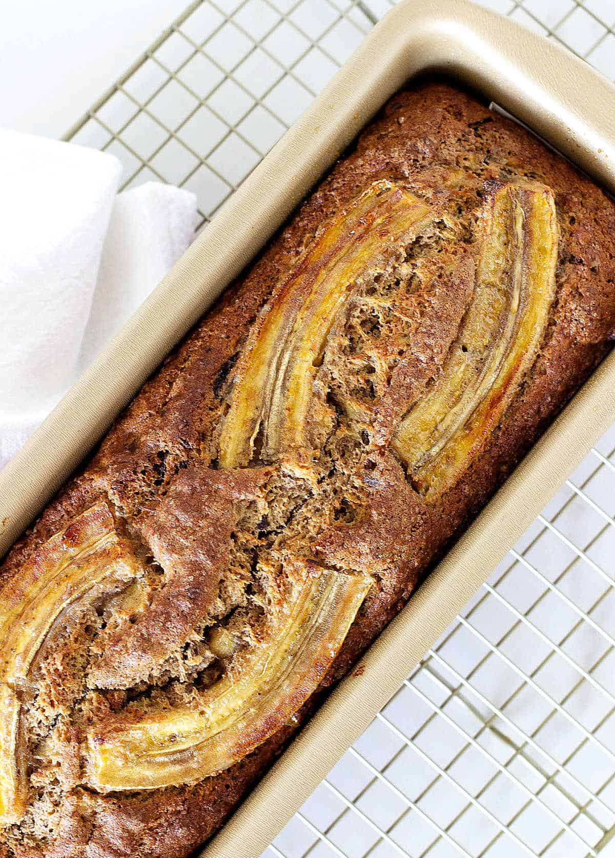 Overview of banana bread in metal pan on white kitchen towel
