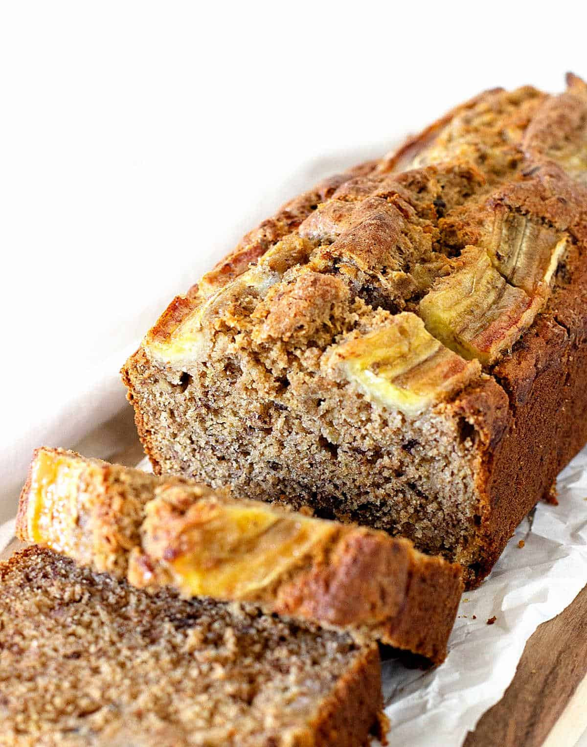 White parchment paper with loaf of banana bread with some cut slices, white background