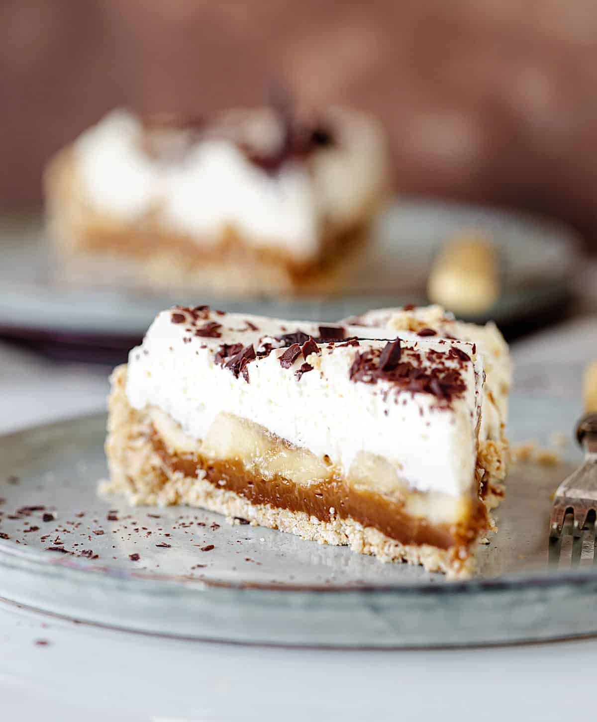 Close up slice of banoffee pie on grey plate, another serving in background