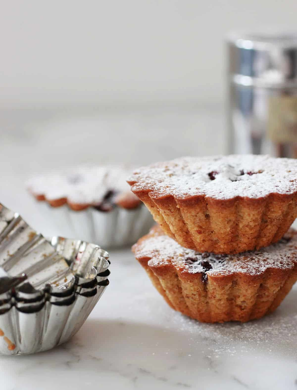 Two stacked mini fluted cakes with metal molds around, grey background
