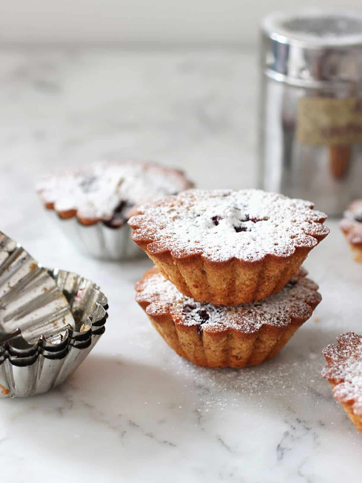 Several mini cakes on white marble surface, fluted molds and sugar shaker