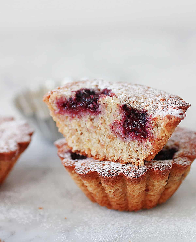 Cut mini blackberry cake on top of whole one, greyish background